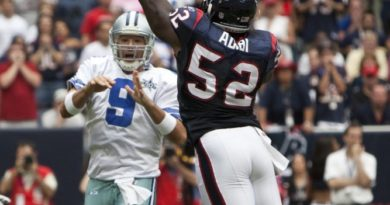 Tony_Romo_tries_to_get_a_pass_over_Xavier_Adibi