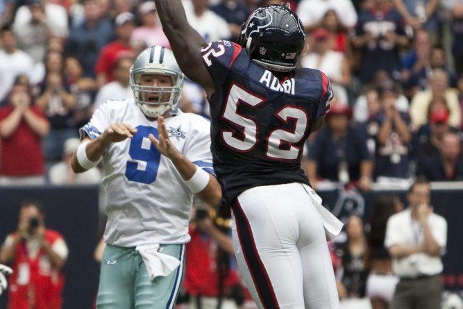 Tony_Romo_tries_to_get_a_pass_over_Xavier_Adibi